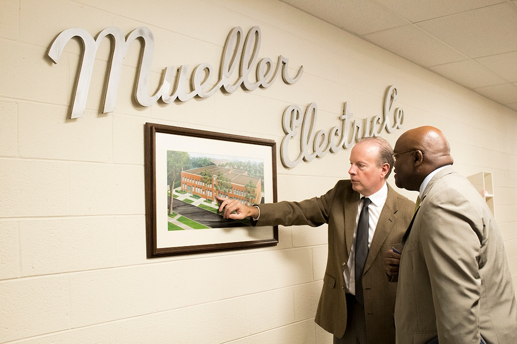 Cliff and Sam examine a picture of the historical company building